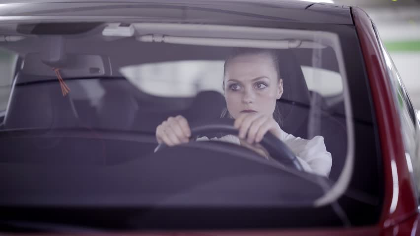 Attractive young blonde woman with pony tail wearing white classic shirt is sitting in red car behind steering wheel when it's starts smoking outside in underground garage.