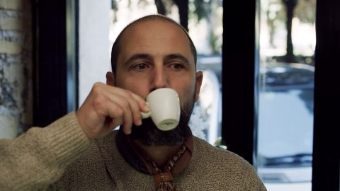 Medium shot on 4k RED camera. In a small coffee shop, a thoughtful Italian man drinks cup with espresso coffee while sitting at the counter.