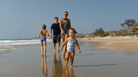 Cute little smiling child running along the beach with big happy healthy family on background and falling down .Slow motion 50Fps.