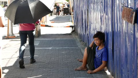 METRO MANILA, PHILIPPINES - CIRCA MARCH 2018: A poor injured young boy sits on the pavement circa March 2018 in Metro Manila, Philippines.