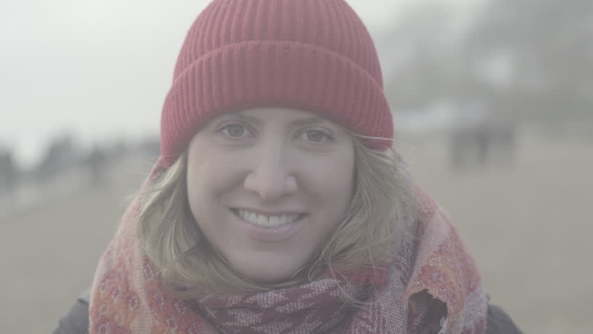 Ungraded, portrait of beautiful woman smiling enjoying cloudy seaside exploring vacation lifestyle with wind blowing hair, girl looking into camera wearing red wool cap and scarf on the beach, slog2   | Shutterstock HD Video #1022825755