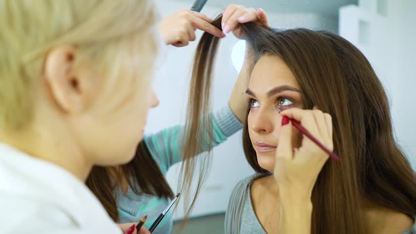 slow motion makeup artist and hairstylist prepare model woman for fashion show