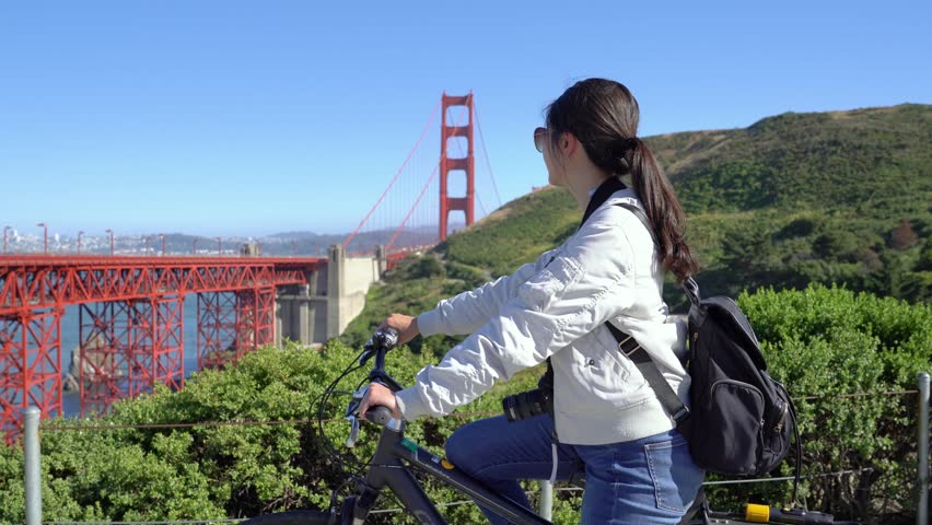 Young girl backpacker passion invited friends join her trip by bicycle visiting golden gate bridge sightseeing on sunny day. asian woman traveler riding bike not alone. beautiful lady with sunglasses | Shutterstock HD Video #1022842255