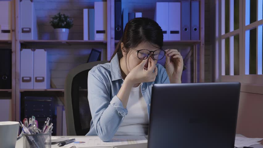 Tired woman suffering eye strain working in night with laptop computer at home. office lady having headache taking down glasses massage nose bridge release pain hurt of head. young people overworked. | Shutterstock HD Video #1022842315