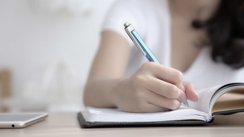Closeup hand of asian woman sitting in the living room study and learning writing notebook and diary on table at home, girl homework, businesswoman planning working on table, education concept. | Shutterstock HD Video #1022850625