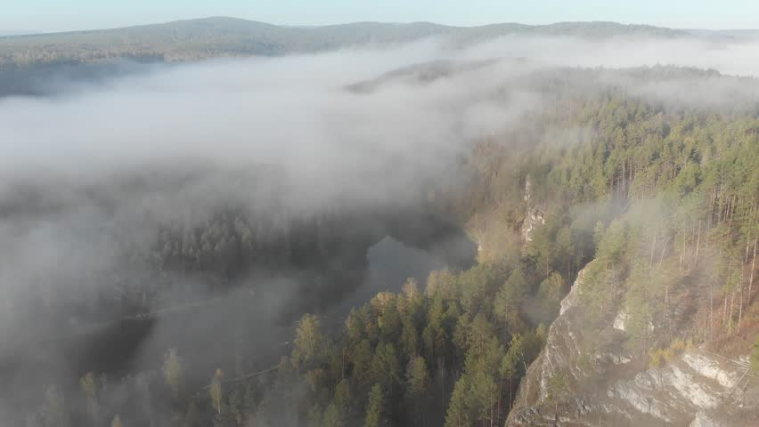 Slow aerial flight backwards over a gentle mountain river, pine forest, clouds. | Shutterstock HD Video #1022855545