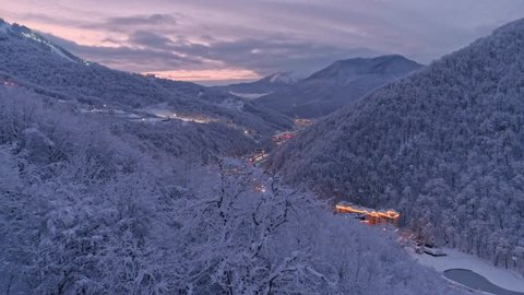Aerial drone establishing shot of white winter Rosa Khutor resort in Sochi. Snow covered trees. Evening illumination. After sunset. Flying low above snow forest