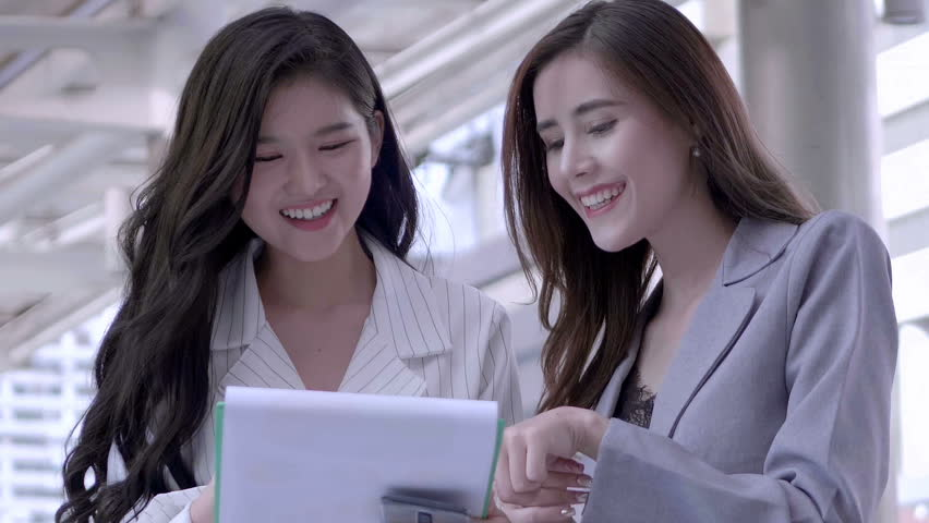Two Businesswomen talking new startup project and smiling happily in city centre Thailand. Business Meeting concept. SLOW MOTION | Shutterstock HD Video #1022861905