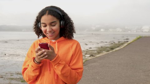 Beautiful mixed race African American girl teenager young woman wearing orange hoodie, walking by a harbor and listening to music on wireless headphones using her smart cell phone