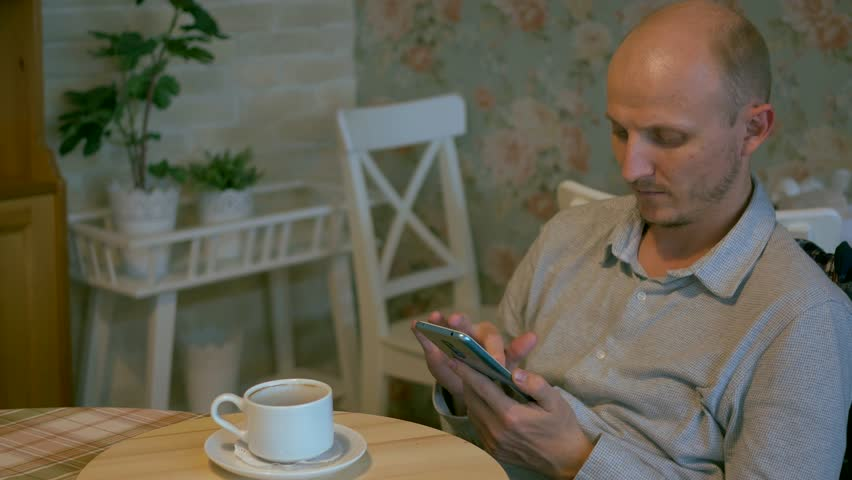 Adult bald male checking smartphone in kitchen with mug of coffee | Shutterstock HD Video #1022892955