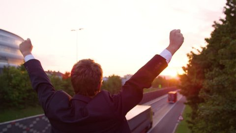 CLOSE UP, SLOW MOTION, SUN FLARE: Golden morning sunbeams shine on excited businessman standing above the highway with outstretched arms. Unrecognizable yuppie celebrating a successful work meeting.