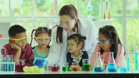 Science teacher and Asian students in science class, they pouring some blue liquid from big beaker into small beaker, concept for study in science class.
