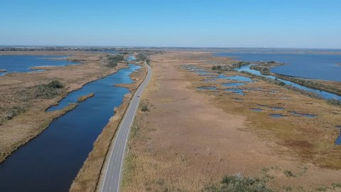 Overhead shot of roadway and car cutting through large marshland area with delta rivers and estuaries deep in the Louisiana bayou on a clear blue day