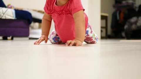 Little girl crawling. Close-up tracking shot of baby's hands and feet when crawling on wooden floor