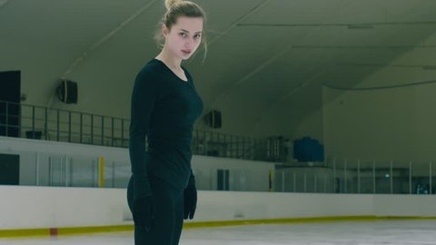 Tilt up shot of young Caucasian figure skater gliding on ice rink, stopping, spraying snow and looking at the camera