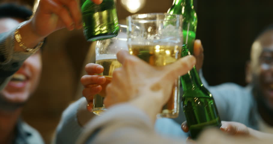 Slow motion  close up of happy young friends having fun together drinking beer and clinking glasses in a pub. Shot in 8K. Concept of friendship, holidays, celebration | Shutterstock HD Video #1022981305