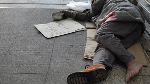 Homeless old man in dirty clothes sleeping on the street and asking for help
