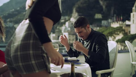 At restaurant with view of coast in the background, a cheating boyfriend sitting with another girl has a drink splashed in his face by his current angry girlfriend. Wide shot on 8k helium RED camera
