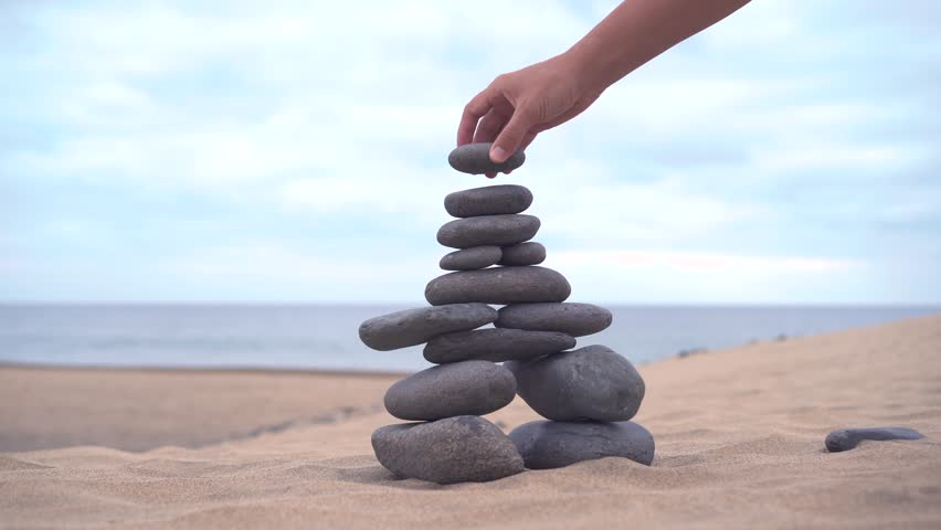 The cairn stands on the sand. The hand adds the last stone to finish the cairn. Sandy desert around | Shutterstock HD Video #1023013345