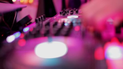 Close-Up of Dj Mixer Controller Desk in Night Club Disco Party. DJ Hands touching Buttons and Sliders Playing Electronic Music