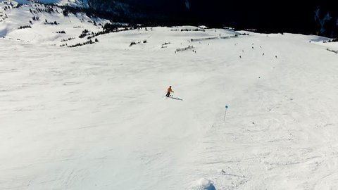 Aerial footage of Blackcomb mountain and skiers on a sunny day.