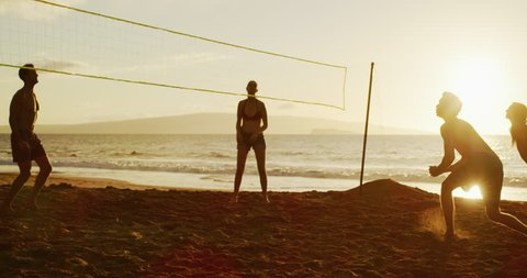 Group of friends playing beach volleyball at sunset, athletic man dives to save volleyball, slowmotion