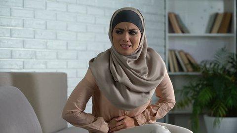 Muslim woman suffering abdominal pain, period cramp, needs medical aid