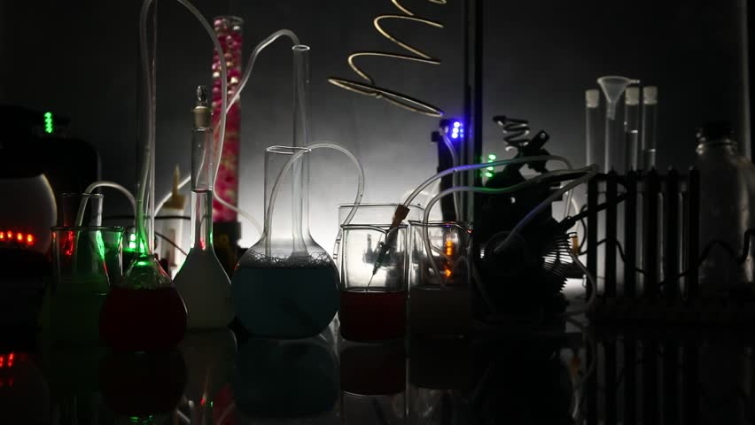 Pharmacy and chemistry theme. Test glass flask with solution in research laboratory. Science and medical background. Laboratory test tubes on dark toned background , science research equipment concept | Shutterstock HD Video #1023111715