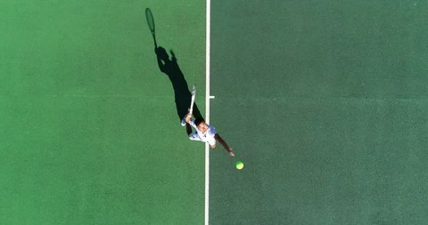 An Asian Tennis Player serves from above and celebrates serving an ace.