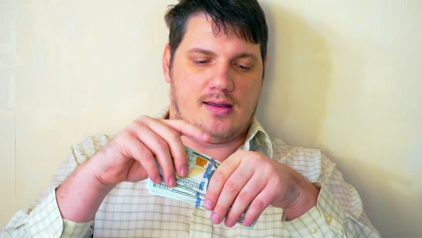 Portrait of a funny man with a stack of hundred dollar bills in his hands | Shutterstock HD Video #1023139705