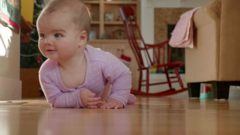 An adorable slow motion shot of a happy baby girl lying in the crib