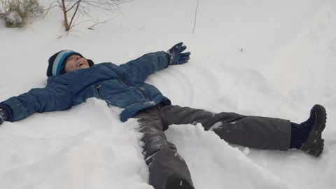 Teenager boy blow snow from hands in winter wood forest park. Caucasian boe fell down. Falling snow angel. Funny happy guy throw snow and falling down