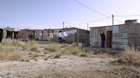Shack dwellers in the door way of a tin shanty at a slum settlement in South Africa.