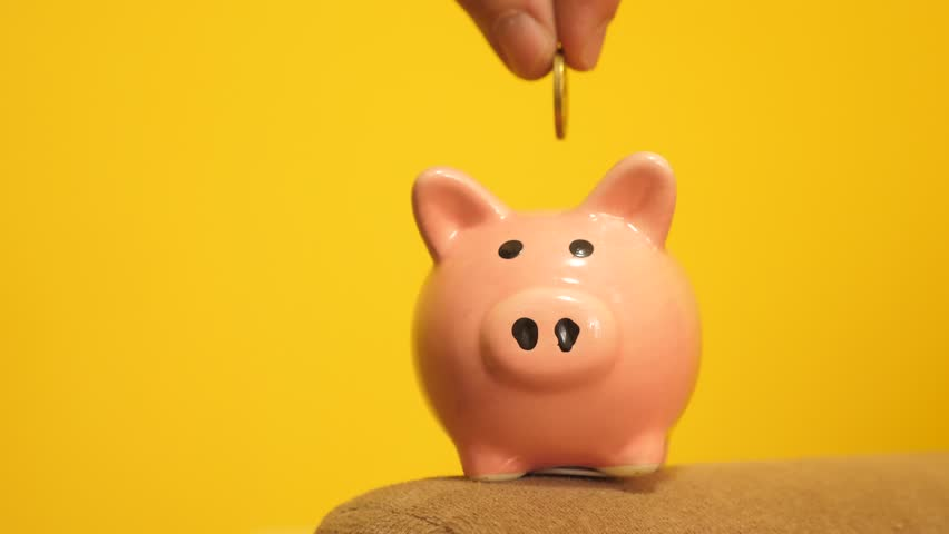 piggy bank business concept. A hand is putting a coin in a piggy bank on a yellow background. saving money is an investment for the future.