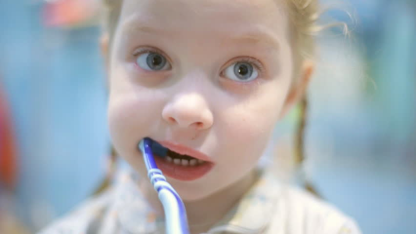 Little girl f brushing her teeth with a toothbrush in bathroom in the morning | Shutterstock HD Video #1023170035