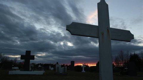 Cemetery cross sliding shot, evil dark cloudy sky red dawn glow, bird flying
