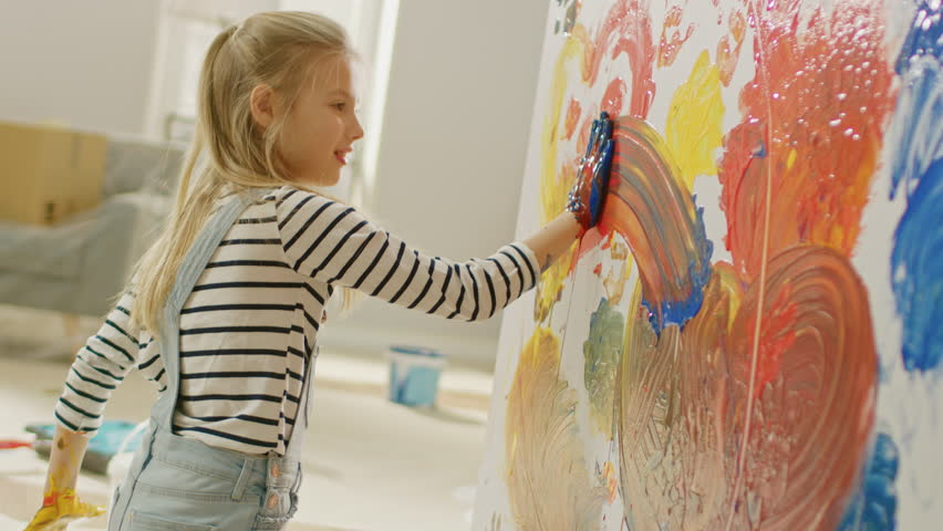 Happy Little Girl with Hands Dipped in Vivid Paint Draws Colorful Abstractions on the Wall. She is Having Fun and Laughs. Home is Being Renovated. | Shutterstock HD Video #1023188095
