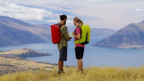 Fit Caucasian adventure couple with backpack reading map on hike of Fjordland The Remarkables Lake Wakatipu New Zealand RED WEAPON