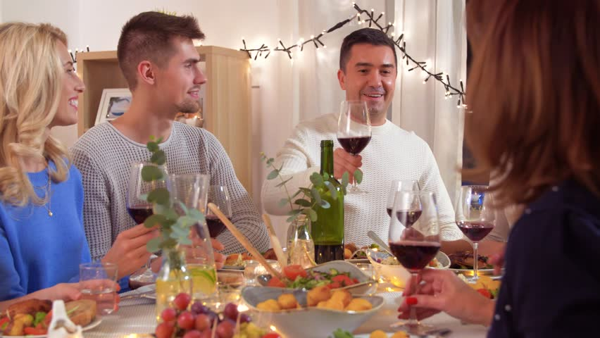 Celebration, holidays and people concept - happy family having dinner party, drinking red wine and toasting at home | Shutterstock HD Video #1023218875