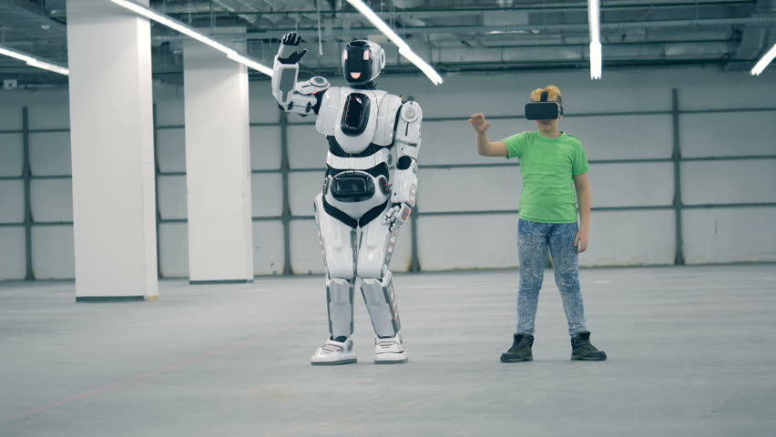 Cyborg is repeating movements after a boy in VR-glasses | Shutterstock HD Video #1023238945