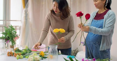 chinese young girl florist is training her friend how to make a beautiful bouquet. she telling her to pick different flowers and colors as collocation, in chengdu china
