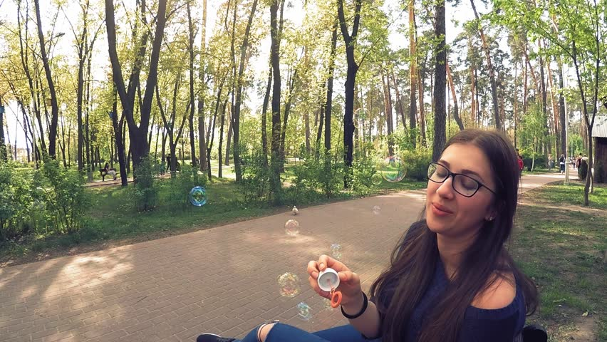 A girl in glasses plays soap bubbles in the park | Shutterstock HD Video #1023265315