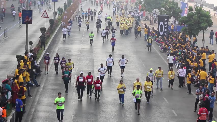 Mumbai, Maharashtra India - January 20th 2019 : Overview shot of a crowd of 100s of people running on the streets of Marine Drive for Tata Mumbai Marathon TMM2019 on a cold winter morning. #1023267235