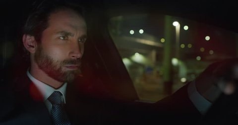 Slow motion of young handsome businessman driving a modern car in center of the city by night. Shot in 8K. Concept of business, success, traveling, luxury