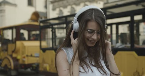 Charming girl in glases walks around the city and listens to the music in her earphones