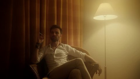 Man Sit On Armchair And Smokes.Man Sits In A Chair And Smoking Cigarette.Man Wearing In White Sits In A Chair.Stylish Man Smokes A Cigarette In Chair.In Chair Sitting Businessman With Cigarette.