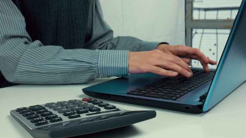 Male hands are typing text on a laptop. White table, calculator, office | Shutterstock HD Video #1023350275