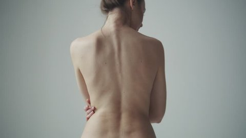 naked female back close-up. girl touches her neck and shoulders