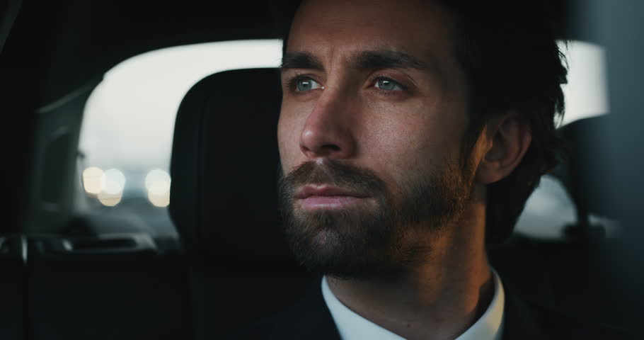 Slow motion close up of young handsome businessman looking outside during traveling in a modern car with a driver in center of the city by day.Shot in 8K.Concept of business,success, traveling luxury  | Shutterstock HD Video #1023373555