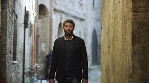 Wide shot on 8k helium RED camera. In a quiet alleyway with stone buildings, an attractive Italian model walks and models his clothing.